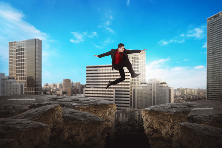 traverse: Asian business man jumping over broken road. Business risk concept