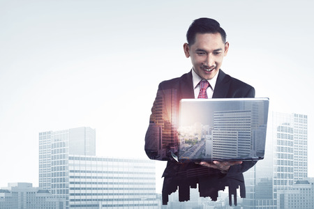 asian business man: Double exposure of asian business man typing with laptop combined with building