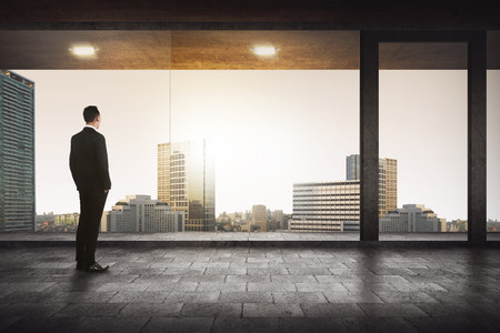 business men: Back view of successful manager looking the city from his office Stock Photo