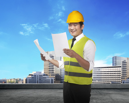 asian architect: Young asian architect looking the blueprint with city background Stock Photo