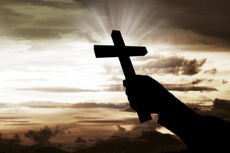 christian faith: Human hand holding christian cross with sky background