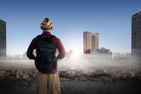 broken back: Back view of traveler wearing hat and backpack looking the broken road Stock Photo
