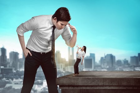 giant man: Giant business man looking at small business woman Stock Photo