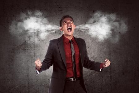 Afbeelding van jonge Aziatische zakenman in woede. Rook uit zijn oren Stockfoto