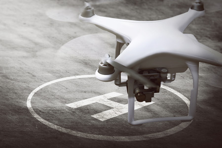 Small drone ready for landing on helipad