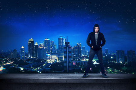 hooded top: Bad guy standing on the building rooftop with city background Stock Photo