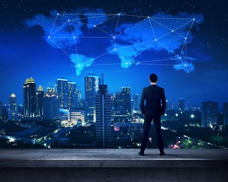 Persona de negocios asiática que se coloca en la azotea con vistas Forma de las nubes y las estrellas mapa mundial Foto de archivo - 54707189