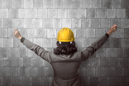 raise hand: Back view architect raise hand looking at the wall Stock Photo