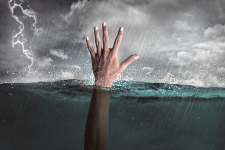 La mano del hombre hacia fuera del agua pidiendo ayuda