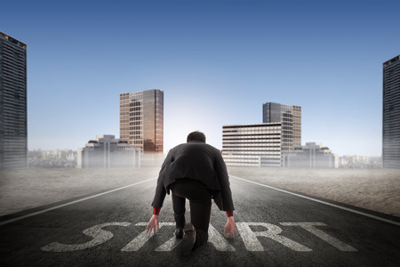 businessman suit: Asian business person ready to run toward the city. Business opportunity concept