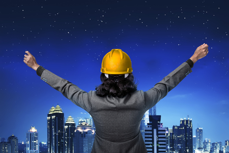 raise hand: Back view architect raise hand looking at the city Stock Photo