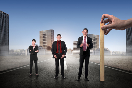 performance appraisal: Hand holding wooden ruler, mesuring employee performance. Working appraisal concept Stock Photo