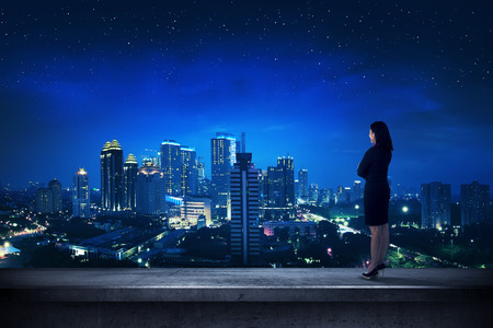 Aziatische business persoon die op het dak kijkt uit op de stad