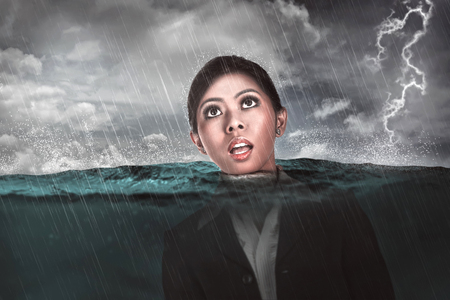 Asian business woman drown in the middle of the sea. Business depression concept Stock Photo