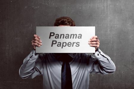 Image du business man holding board couvrant son visage avec papiers panama texte Banque d'images