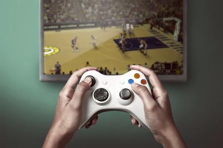 jugando videojuegos: controlador de consola de la explotaci�n del juego jugando juego de deportes en la televisi�n Foto de archivo