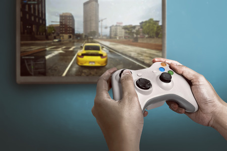 Hand holding game console controller playing racing game on the television