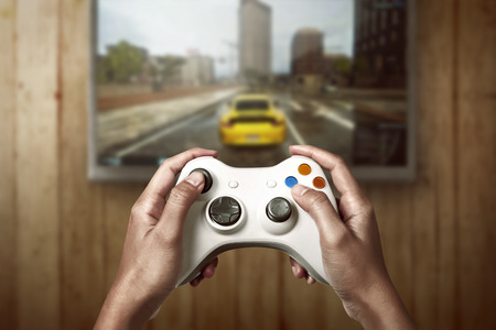 gaming: Hand holding game console controller playing racing game on the television