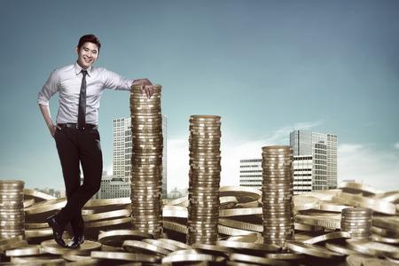 Aziatische zakenman leunend op de stapel munten. Business succes concept