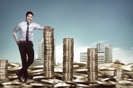 Asian business man leaning on the pile of coins. Business success concept Archivio Fotografico