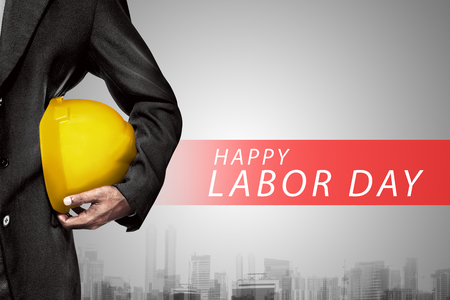 Hand or arm of engineer hold yellow plastic helmet for worker. Labor day concept Foto de archivo