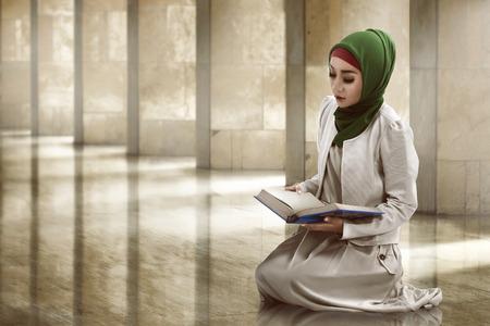 jilbab: Woman reading koran inside of the mosque Stock Photo