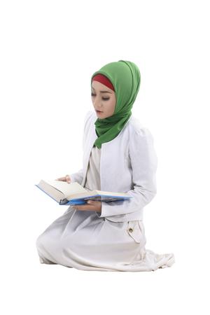 jilbab: Muslim woman reading koran isolated over white background