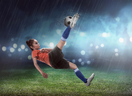 Aziatische vrouw voetballer kick bal op het stadion