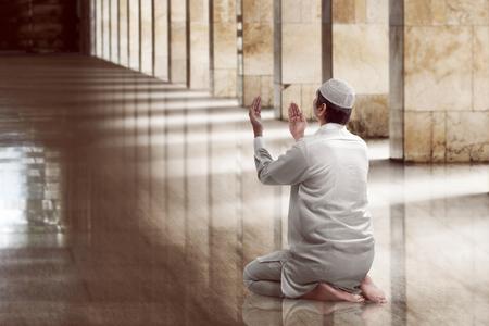 Hombre musulmán orando religiosa dentro de la mezquita Foto de archivo - 56192564