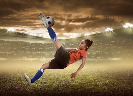 Asian woman football player kick ball on the stadium