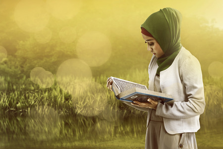 koran: Image of asian muslim woman reading koran