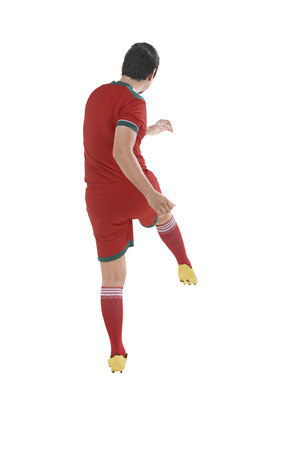 kick ball: Back view of asian football player kick ball isolated over white background