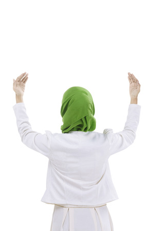 religious clothing: Back view of muslim woman praying isolated over white background