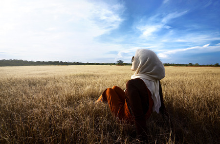 Moslim vrouw die hijab ontspannen op savanne bij Sumba Indonesië Stockfoto