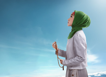 religious clothing: Young muslim woman holding prayer beads over blue sky