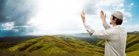 hombre orando: Imagen de hombre musulmán joven que ruega en la montaña Foto de archivo