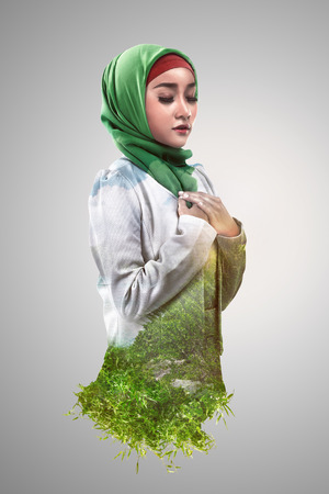 jilbab: Image of double exposure muslim woman with green grass and blue sky Stock Photo