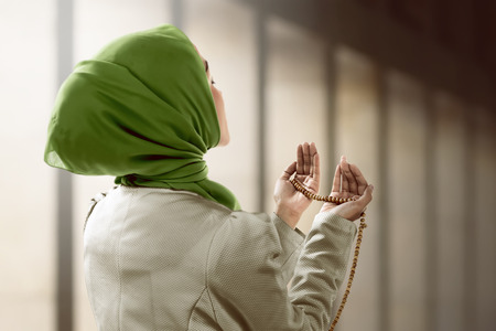 Young muslim woman holding prayer beads over mosque background Archivio Fotografico