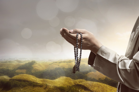 islamic pray: Hand of muslim people praying with hill landscape background Stock Photo