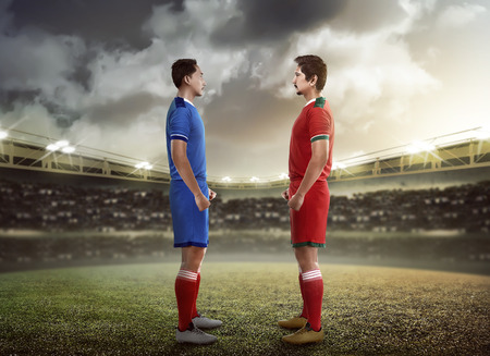 kickoff: Two football player facing each other on the kickoff at the stadium Stock Photo