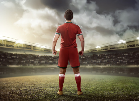 back light: Asian football player standing on green grass stadium
