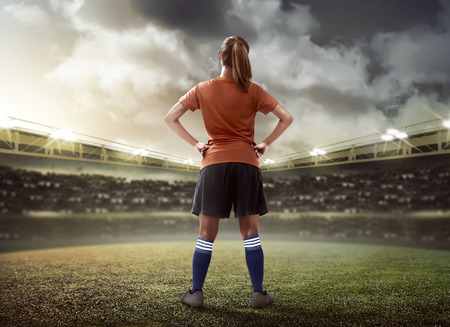 Back view of female football player standing on the field