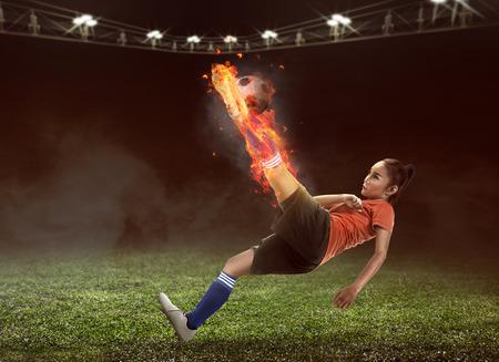 action girl: Asian woman football player kick fire ball on the stadium