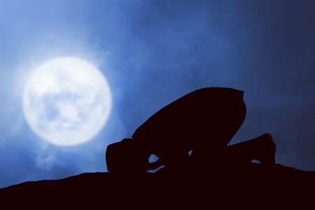 man in the moon: Image of silhouette man praying with full moon background Stock Photo