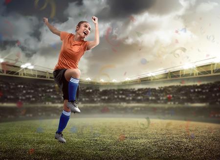 female soccer: Image of happy female soccer player on the stadium