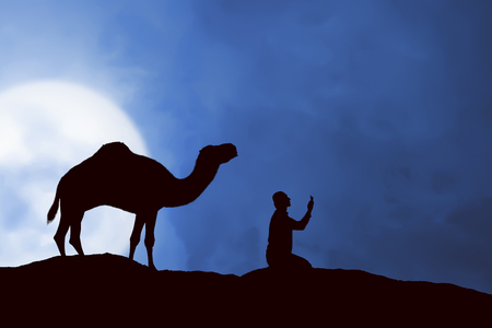person silhouette: Image of silhouette man praying and camel with full moon background Stock Photo