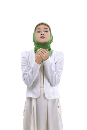 religious clothing: Young muslim woman praying isolated over white background