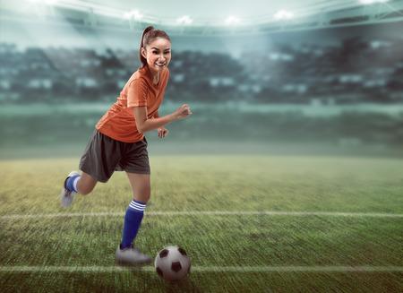 dribbling: Image of female football player dribbling ball on the stadium Stock Photo