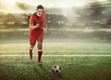 dribbling: Image of football player dribbling ball on the field