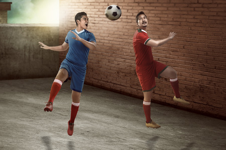 football play: Image of soccer player header on the alley. Street soccer concept Stock Photo
